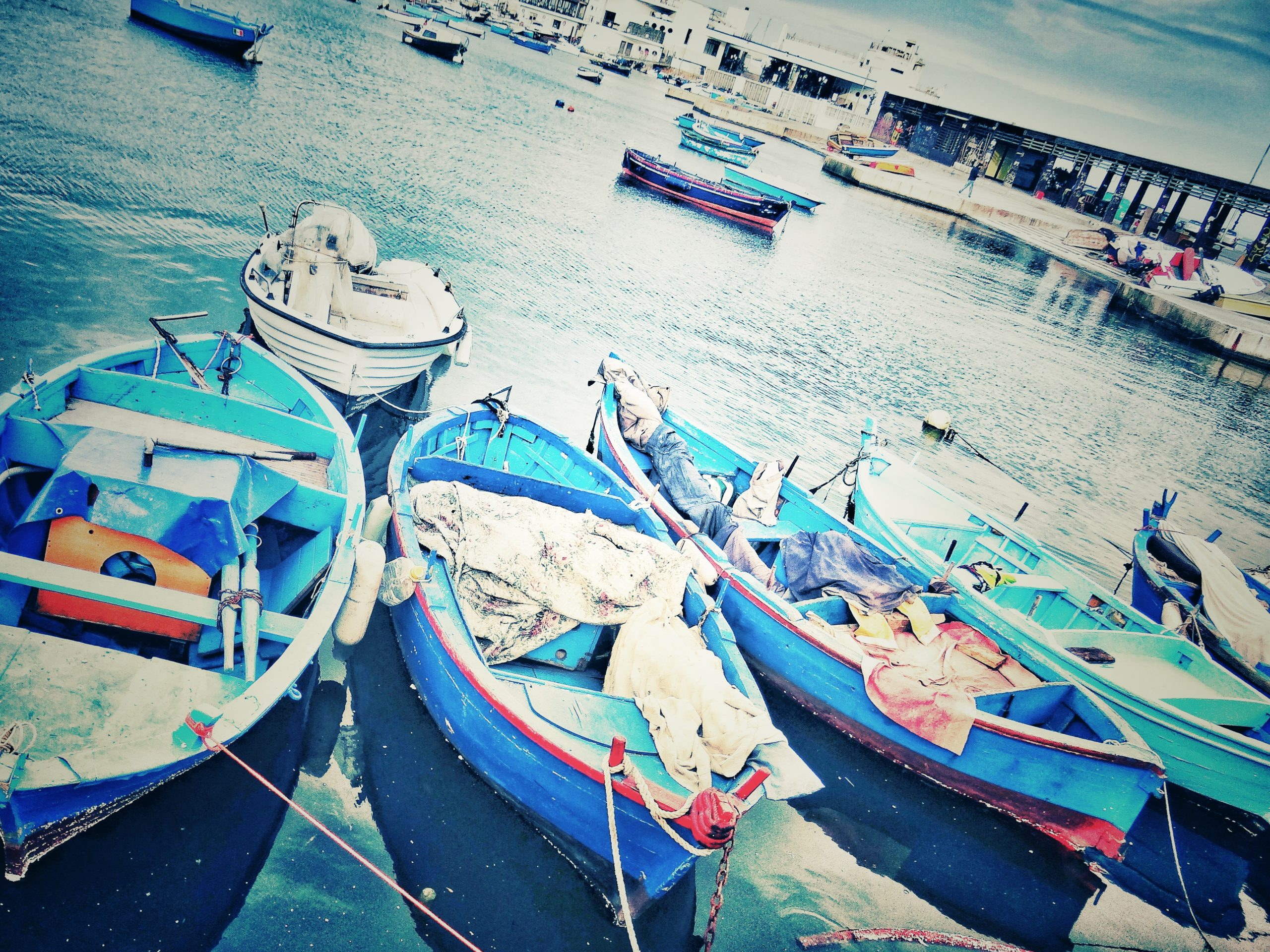 Blue fishing boats at the old port in Bari.